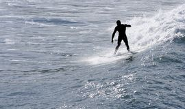 Sport sea Surfing. A man riding a wave with his surfing board Stock Image