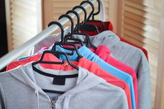 Row of sport shirts and jackets hanging on clothes rack at a fashion store. Sport shirts and jackets hanging on clothes rack at a fashion store Stock Photo