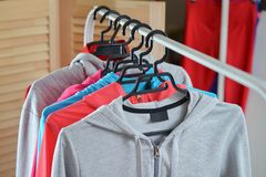 Sport shirts and jackets hanging on clothes rack at a fashion store Royalty Free Stock Image