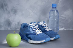 Sport shoes, apple, bottle of water on gray concrete backround. Stock Image