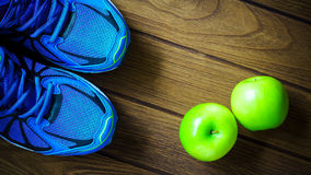 Sport shoes and apples on a wooden background. Sport equipment stock photo