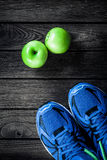 Sport shoes and apples  on a  wooden background. Sport equipment. Healthy and active lifestyles, copy space for text. Conceptual photo. Top view Royalty Free Stock Image