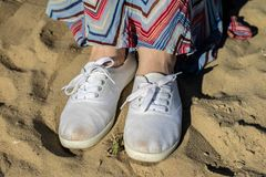 Sport shoes on the beach. Women& x27;s shoes on a beautiful spring da. Y. Season of the spring royalty free stock photo