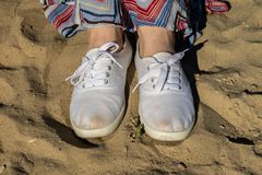 Sport shoes on the beach. Women& x27;s shoes on a beautiful spring da. Y. Season of the spring stock images