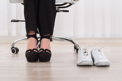 Sport Shoes Besides Businesswoman`s Foot. Pair Of A White Sport Shoes Besides Businesswoman`s Foot Wearing High Heels Royalty Free Stock Image