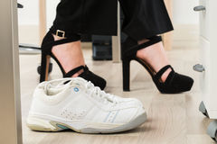 Sport Shoes Besides Businesswoman`s Foot. Pair Of A White Sport Shoes Besides Businesswoman`s Foot Wearing High Heels Stock Photos