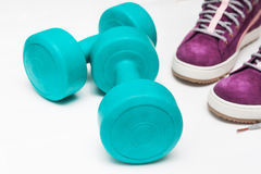 Sport shoes and  blue dumbbell on white background Royalty Free Stock Images