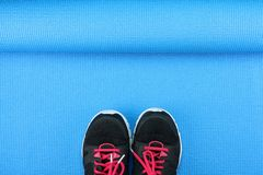 Sport shoes on blue yoga mat background, Fitness accessories. Sport shoes on blue yoga mat background, Fitness accessories and exercise Equipment, No gym Stock Image