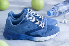 Sport shoes, bottle of water, apples on gray concrete backround. Royalty Free Stock Images