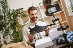 Sport shoes. Cheerful male blogger holding black sneakers while recording new video for his blog. Fashion. Beauty. Video review royalty free stock photo