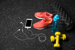 Sport shoes, dumb-bells, pilates mat, blue bottle, and phone with headphones on a black background. Sport concept. A colorful set of sportive accessories for Stock Photos