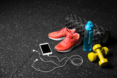 Sport shoes, dumb-bells, pilates mat, blue bottle, and phone with headphones on a black background. Training concept. A colorful set of sportive accessories for Royalty Free Stock Image