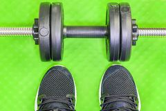 Sport shoes and dumbbell on green Royalty Free Stock Photos