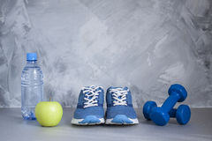 Sport shoes, dumbbells, apple, bottle of water on gray concrete Stock Photography