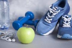 Sport shoes, dumbbells, earphones, apple, bottle of water on gra Stock Image