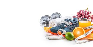 Sport shoes dumbbells fresh fruit measure tape and multivitamin juice isolated on white background. Healthy sport and diet concept royalty free stock image