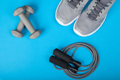 Sport shoes, dumbbells and skipping rope on blue background. Top view. Fitness, sport and healthy lifestyle concept. royalty free stock photography