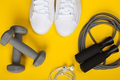 Sport shoes, dumbbells and skipping rope on yellow background. Top view. Fitness, sport and healthy lifestyle concept royalty free stock photo