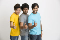Three young friends happy and showing thumbs up Royalty Free Stock Images