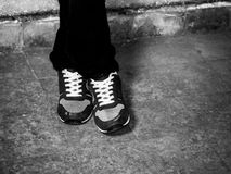 Sport shoes legs crossed in black and white Stock Photo