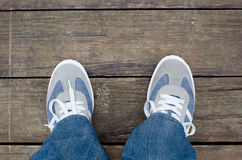 Sport shoes and legs in jeans from above on wooden dock floor.  Stock Photo
