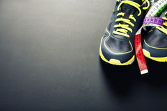 Sport shoes and measuring tape Royalty Free Stock Photos