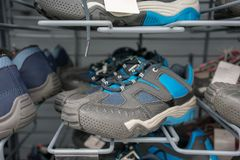 Sport shoes on metal shelves at store. Sport shoes in blue color on grey metal shelves at store Royalty Free Stock Photography