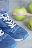 Sport shoes, meter, apples, bottle of water on gray concrete backround. Concept healthy lifestyle, sport and diet. Focus is only on the sneakers stock photography