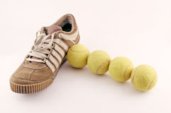 Sport shoes next to 4 tennis balls stock photography
