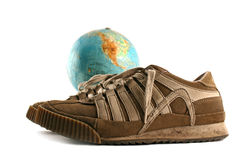 Sport shoes next to a globe Royalty Free Stock Image