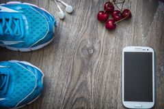 Sport shoes, phone and smart watch with set for sports activities on floor. stock images