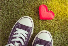 Sport shoes and red heart on grass background Royalty Free Stock Photography