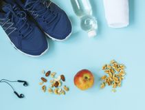 Sport shoes, skipping rope, nuts, headphones, apple and bottle of water on blue background. stock image