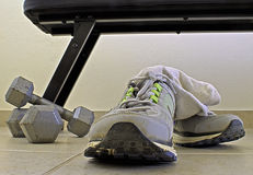Sport Shoes. Sport sneakers in front of a pair of dumbbells and a weightlifting bench Royalty Free Stock Image