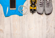 Sport shoes with sports equipment on wooden floor. Royalty Free Stock Photo