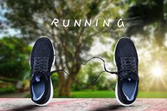 Sport shoes standing on old grunge sport floor with heart shaped lace with text running on blurred park with soft sunlight Stock Photo