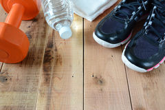 Sport shoes and towel, dumbbell, bottle of water on wooden. Stock Image