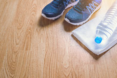 Sport shoes, water, towel on wooden background Stock Photos