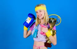 Sport shop assortment. Girl successful modern woman hold golden goblet of sport champion and equipment blue background royalty free stock images