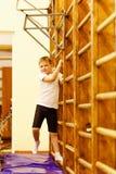 Sport siedmioletnia chłopiec w białej koszulce czarnych skrótach i angażuje na szwedzi ścianie w gym zdjęcia stock