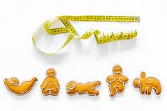 Sport for slimming concept. Yoga asanas cookies and measure tape on white background top view Royalty Free Stock Photos