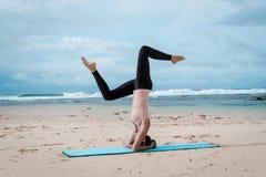Sport, sprawność fizyczna, joga, ludzie i zdrowia pojęcie, - młoda kobieta robi headstand ćwiczeniu na plażowym tle obraz stock