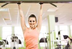 Sport, sprawność fizyczna, bodybuilding, praca zespołowa i ludzie pojęć, - młoda kobieta napina mięśnie na gym maszynie Zdjęcie Royalty Free