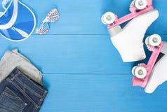 Sport, stile di vita sano, fondo di pattinaggio a rotelle Pattini di rullo bianchi, insieme dell'abbigliamento, occhiali da sole  Immagini Stock