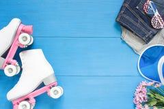 Sport, stile di vita sano, fondo di pattinaggio a rotelle Pattini di rullo bianchi, insieme dell'abbigliamento, occhiali da sole  Fotografie Stock Libere da Diritti
