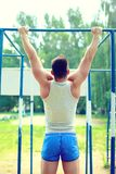 Sport, street workout concept - athlete doing pull ups on the horizontal bar. Outdoors Royalty Free Stock Photo