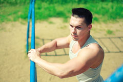 Sport, street workout concept - sportsman near the horizontal bar Stock Photos