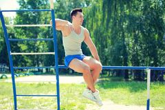 Sport, street workout concept - sportsman sitting on the horizontal bar Royalty Free Stock Photography