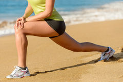 Sport and stretching concept on summer. Sport concept. Woman stretching legs on beach in summer. Female athlete warming up before running stock photography
