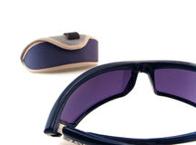 Sport sunglasses with case. Close-up photo of blue sunglasses with a slightly blurred case in the background stock photos